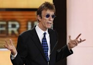 Robin Gibb, pictured in 2011, singer with the legendary band the Bee Gees, was visited by his wife and youngest son in the hospital on Monday as he remained in a coma, having contracting pneumonia in his battle against cancer
