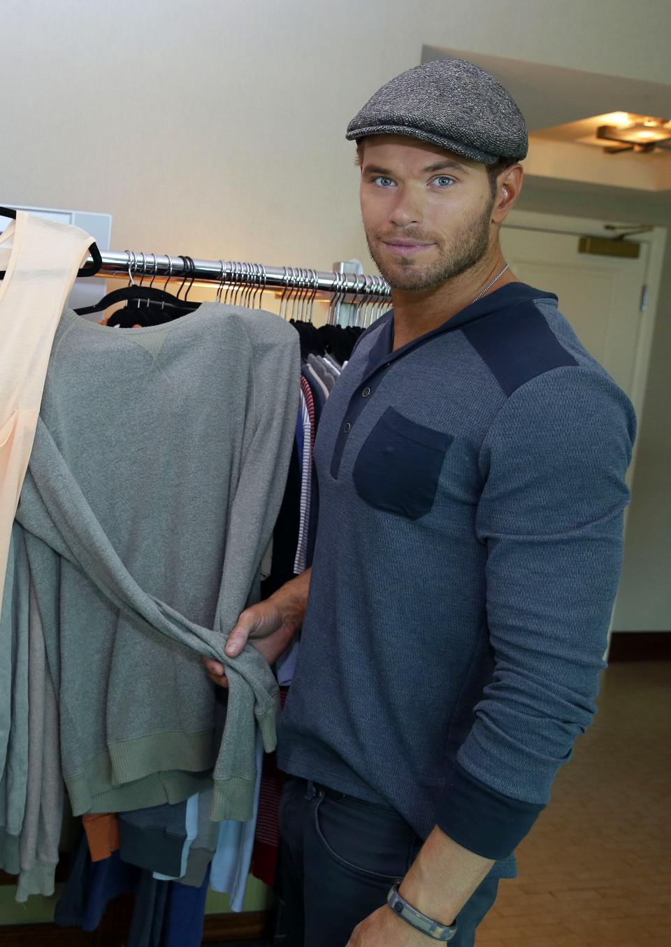 Actor and designer Kellan Lutz poses with selections from his pre-spring 2014 clothing line Abbot + Main at the Mandalay Bay Hotel on Monday, Aug. 19, 2013 in Las Vegas. (Photo by Isaac Brekken/Invision/AP)