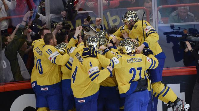 Team Sweden, with golden helmets, celebrates after defeating Team Switzerland during third period gold medal game action at the world hockey championship in Stockholm, Sweden, on Sunday, May 19, 2013.  (AP Photo/The Canadian Press, Jacques Boissinot)