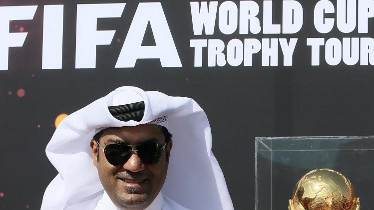 Official stands near the FIFA World Cup trophy following its arrival in Doha on a tour