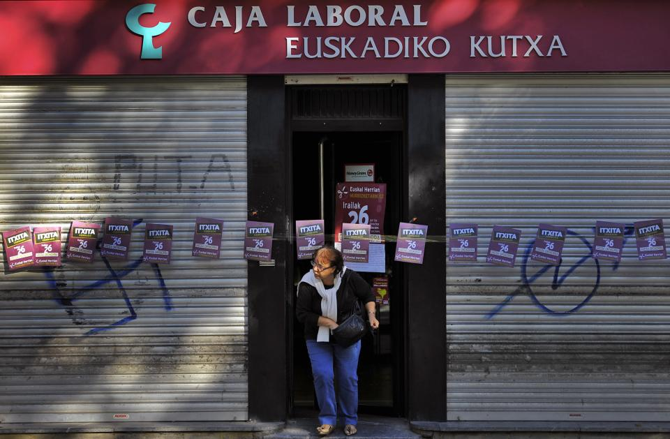 A woman leaves the doorway of a Basque Bank, closed during a general strike in the Basque Country and Navarra Province, against austerity measures by the Spanish Government, in San Sebastian, northern Spain, Wednesday, Sept. 26, 2012. (AP Photo/Alvaro Barrientos)