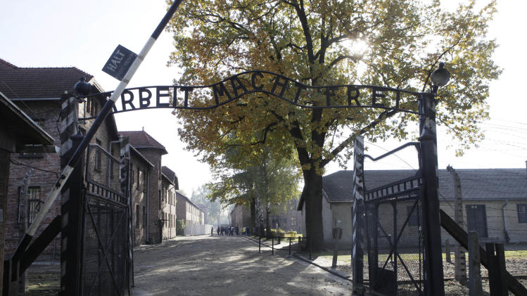 "FILE - In this Oct. 19, 2012 file photo the entrance with the inscription ""Arbeit Macht Frei"" (Work Sets You Free) gate of the former German Nazi death camp of Auschwitz is pictured at the Auschwitz-Birkenau memorial in Oswiecim, Poland. A 94-year-old man, deported from the U.S. for lying about his Nazi past, is unfit for trial on allegations he was an accessory to thousands of murders as an SS guard at Auschwitz, a German court said Friday, Feb. 28, 2014. The Ellwangen state court said Hans Lipschis is suffering from ""worsening dementia"" and could not be tried. He was charged with 10,510 counts of accessory to murder on allegations he served as a guard at the death camp from 1941 to 1943. (AP Photo/Czarek Sokolowski, File)"