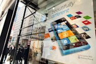 People walk past an advertisement for the Nokia Lumia 900 phone, which runs on a Windows platform, in the window of an AT&T store on April 9 in New York City. Shares in beleaguered telecom giant Nokia plunged to a 16-year low on Monday after Microsoft said its Windows 8 upgrade would not work on the Lumia 900 model