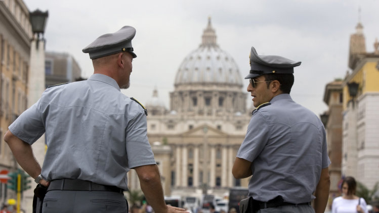 FILE - In this Tuesday, Sept. 21, 2010, file photo, Italian financial police officers talk to each other in front of St. Peter's Square at the Vatican. The Vatican took another step in its efforts to be more financially transparent by publishing a first-ever annual report for the Vatican bank on Tuesday, Oct. 1, 2013. It comes as Italian prosecutors investigate alleged money-laundering there, a Vatican monsignor remains in detention and the pope himself probes the problems that have brought such scandal to the institution. (AP Photo/Angelo Carconi, File)
