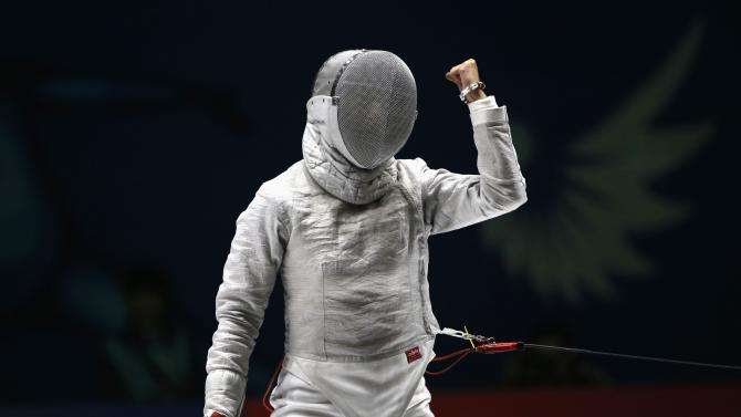 South Korea's Lee reacts after defeating her compatriot Kim at the final of their sabre bout in the women's individual competition at Goyang Gymnasium, during the 17th Asian Games