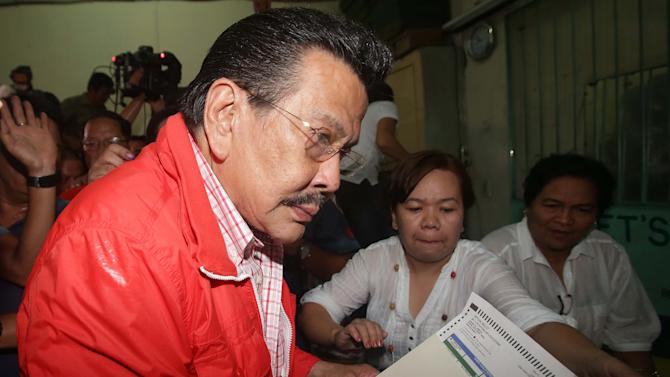 Former Philippine President Joseph Estrada, who is running for mayor of Manila, prepares to enter his vote at a school used as a voting center during mid-term elections in Manila, Philippines on Monday, May 13, 2013. The country is electing local officials from senators to congressmen and down to municipal mayors during Monday's mid-term elections. (AP Photo/Aaron Favila)