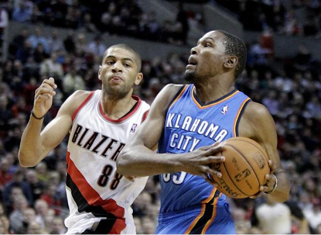Oklahoma City Thunder forward Kevin Durant, right, drives to the basket on a fast break past Portland Trail Blazers forward Nicolas Batum, from France, during the first half of an NBA basketball game