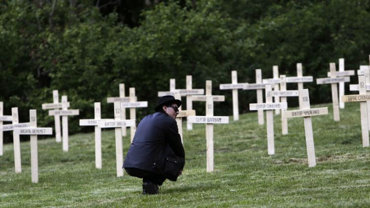 A man pays his respect in front of a 107 wooden crosses, which honour victims of recent protests in Ukraine in Prague