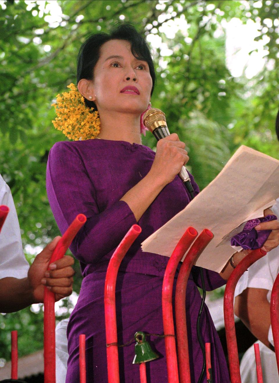 FILE - In this Saturday, May 25, 1996 file photo, Burmese pro-democracy leader Aung San Suu Kyi makes her weekly speech at the gate of her residential compound in Rangoon, Burma. (AP Photo/Richard Vogel)