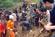 Rescuers are seen searching for victims after a landslide, triggered by sustained rains on October 4, buried a school and three farmhouses in Yiliang, southwest China's Yunnan province. The bodies of all 18 schoolchildren buried under a landslide in China have been recovered, officials said, as authorities defended returning them to school following recent deadly earthquakes