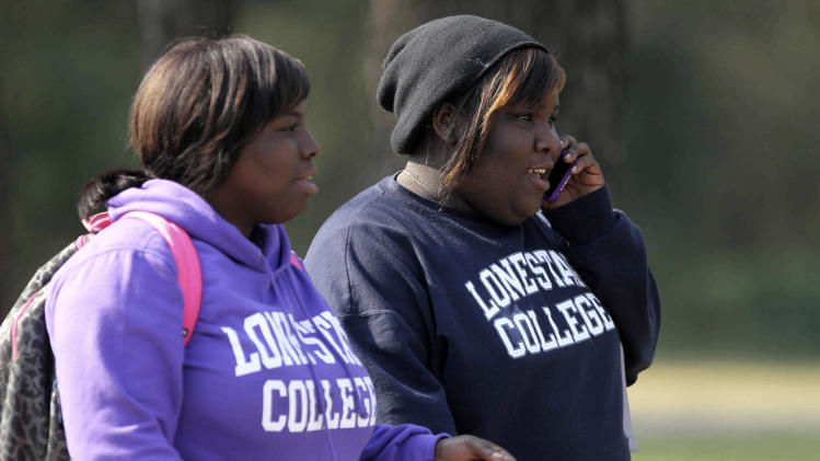 Women wearing Lone Star College sweatshirts walk near Lone Star College in Houston, which was placed on lockdown Tuesday, Jan. 22, 2013, after a shooting that wounded three people and sent students fleeing for safety. (AP Photo/The Courier of Montgomery County, Jason Fochtman)
