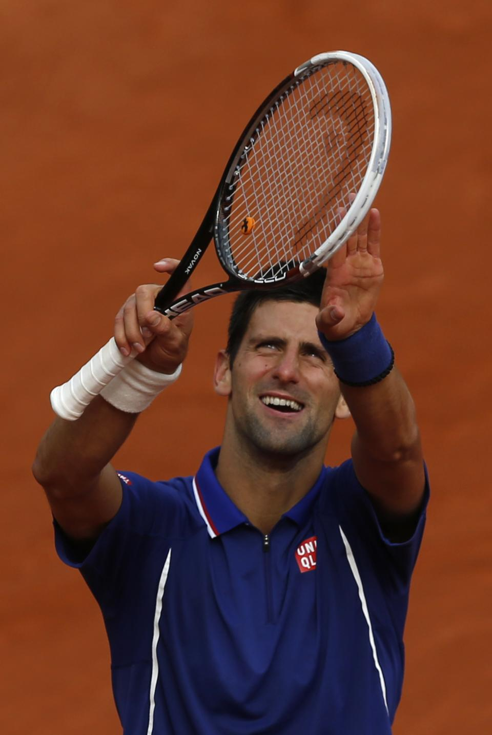 Serbia's Novak Djokovic mimics pushing the rain clouds away shortly before defeating Argentina's Guido Pella during their second round match of the French Open tennis tournament at the Roland Garros stadium Thursday, May 30, 2013 in Paris. Djokovic won 6-2, 6-0, 6-2. (AP Photo/Petr David Josek)