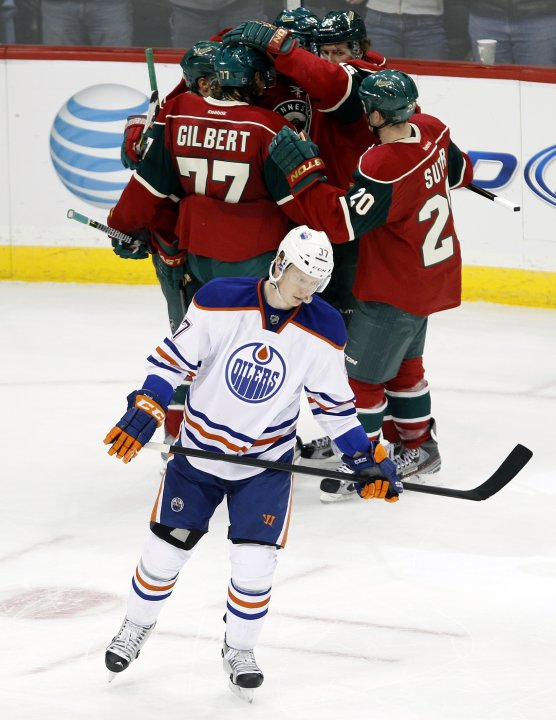 Edmonton Oilers left wing Lennart Petrell skates past Minnesota Wild Dany Heatley as he celebrates his goal with teammates in St. Paul