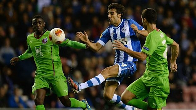 Wigan Athletic's Jordi Gomez (C) is challenged by FC Rubin Kazan's Chris Mavinga (L) and Ivan Marcano during their Europa League soccer match at the DW Stadium in Wigan, northern England, October 24, 2013. (Reuters)