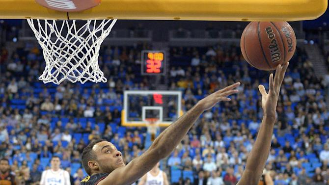 UCLA guard Norman Powell, right, shoots as Southern California guard Julian Jacobs, center, defends and guard Isaac Hamilton watches during the first half of an NCAA college basketball game, Wednesday, March 4, 2015, in Los Angeles. (AP Photo/Mark J. Terrill)