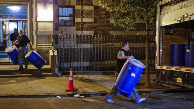 """Members of a cleaning crew with """"Bio Recovery Corporation"""" load barrels into a truck after taking them from the building where Dr. Craig Spencer lives in New York"""