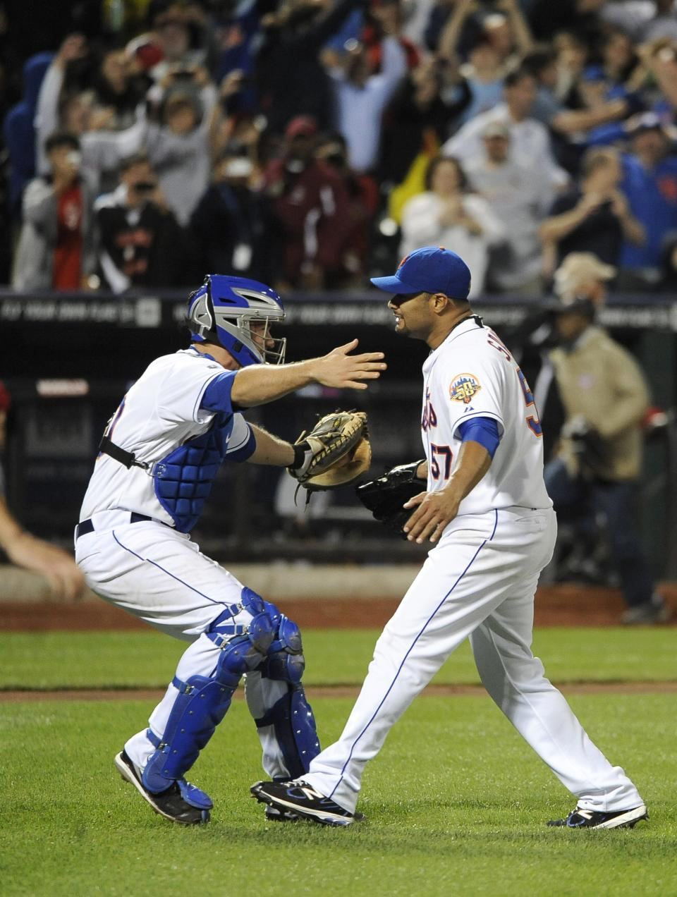 New York Mets catcher Josh Thole, left, runs to hug starting pitcher Johan Santana who threw a no-hitter against the St. Louis Cardinals in a baseball game on Friday, June 1, 2012, at Citi Field in New York. (AP Photo/Kathy Kmonicek)