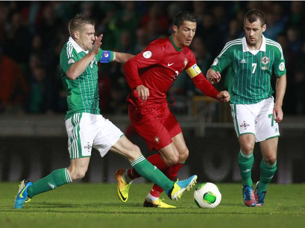 Portugal's Cristiano Ronaldo is challenged by Northern Ireland's Steven Davis and Niall McGinn during their 2014 World Cup qualifying soccer match at Windsor Park Stadium in Belfast.
