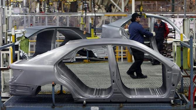 An Auto worker loads bodyshells of a Toyota Camry Hybrid car onto the assembly line at the Toyota plant in Melbourne