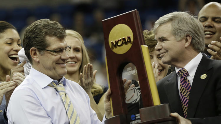 Connecticut head coach Geno Auriemma receives the championship trophy of the women's Final Four of the NCAA college basketball tournament, Tuesday, April 9, 2013, in New Orleans. Connecticut defeated Louisville 93-60. (AP Photo/Dave Martin)