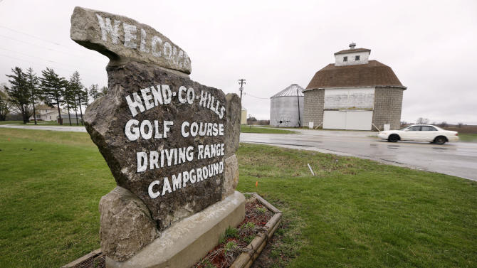 In this Wednesday, April 10, 2013 photo, a sign for the Hend-Co-Hills Golf Course sits near a storage barn on a farm, in Biggsville, Ill. Farmer Clark Kelly purchased the course, which was in foreclosure, with plans to plow it into farm land. Across the Midwest, farmers are planting crops on almost any scrap of available land to take advantage of consistently high corn and soybean prices. (AP Photo/Charlie Neibergall)