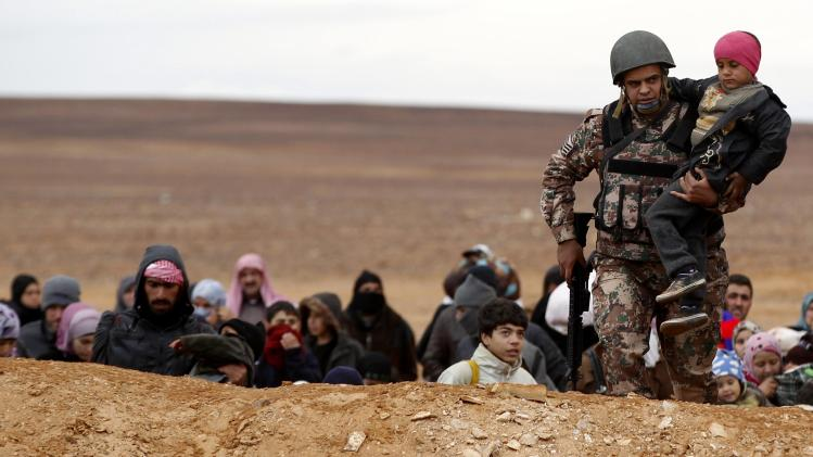 Jordanian soldier carries a Syrian refugee child as they walk with Syrian refugees near Ruwaished
