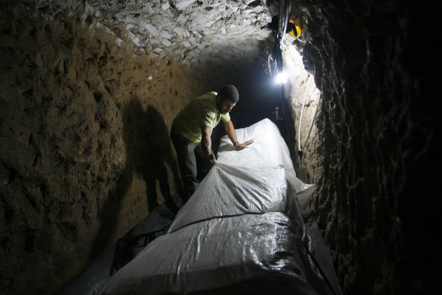 In this Thursday, Oct. 28, 2010 file photo, a Palestinian smuggler moves refrigerators through a tunnel from Egypt to the Gaza Strip under the border in Rafah, southern Gaza Strip. Hamas had hoped the Islamists who took charge in Egypt this summer -- fellow members of the region&#39;s Muslim Brotherhood -- would swiftly turn the shared border crossing into a free-flowing trade route, ending Gaza&#39;s five-year isolation from the world and making the tunnels obsolete. (AP Photo/Eyad Baba, File)