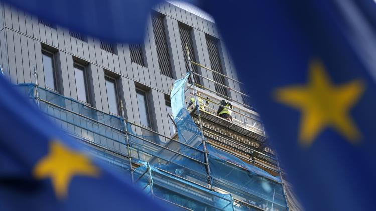 European Union flags flutter as construction workers are seen on a building under renovation in Brussels