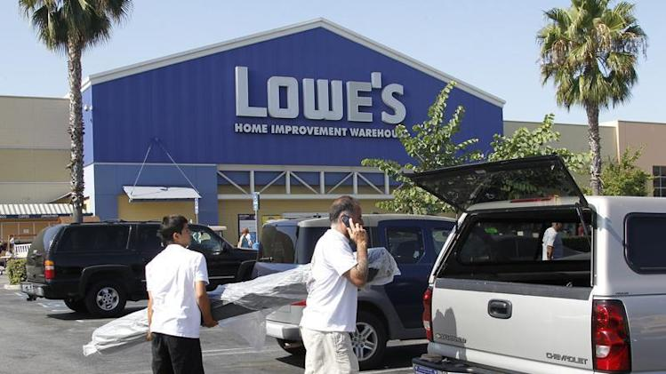 People load a roll of carpet into a vehicle at the Lowe's Home Improvement Warehouse in Burbank