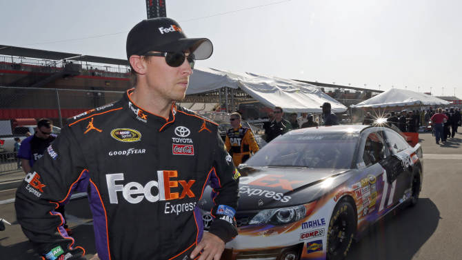 FILE - In this March 22, 2013, file photo, Denny Hamlin stands in the garage area after taking the pole position in his FedEx Express Toyota for the NASCAR Sprint Cup series Auto Club 400 auto race in Fontana, Calif. NASCAR is not penalizing Tony Stewart for scuffling with Joey Logano on pit road at California, and viewed the crash between Logano and Denny Hamlin as a racing incident. AP Photo/Reed Saxon, File)