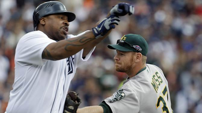 Detroit Tigers designated hitter Delmon Young, left, is tagged out by Oakland Athletics first baseman Brandon Moss (37), allowing teammate Miguel Cabrera to score from third, during the third inning of Game 2 of the American League division baseball series on Sunday, Oct. 7, 2012, in Detroit. (AP Photo/Paul Sancya)