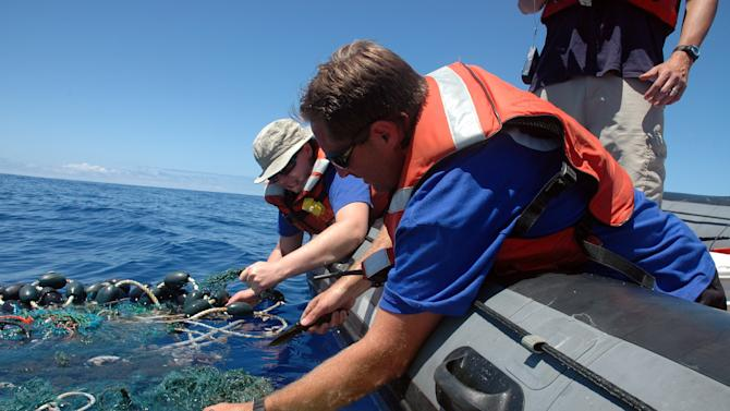 File - In this Aug. 11, 2009 file photo provided by the Scripps Institution of Oceanography shows Matt Durham, center, pulling in a large patch of sea garbage with the help of Miriam Goldstein, right, in the Pacific Ocean. Plastics discarded by people often end up in the ocean, creating coastal pollution that harms marine life and gathers out at sea in what's become known as the great Pacific garbage patch. Now, California state lawmakers have introduced a law that if passed would require makers of plastic bottles, bags and packaging to replace plastics with more environmentally friendly alternatives. (AP Photo/ Scripps Institution of Oceanography, Mario Aguilera, File)