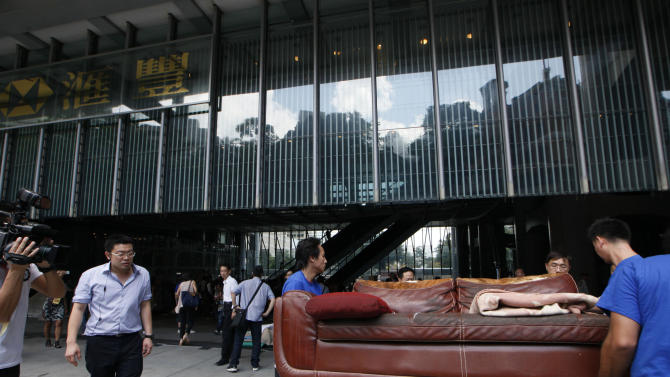 Bailiffs move away protesters' belongings from a public space underneath HSBC's Asian headquarters Tuesday, Sept. 11, 2012. Hong Kong's Occupy activists were locked in a standoff Tuesday with bailiffs trying to evict them from the site. The protesters had ignored a court order requiring them to leave the site by Aug. 27. (AP Photo/Kin Cheung)