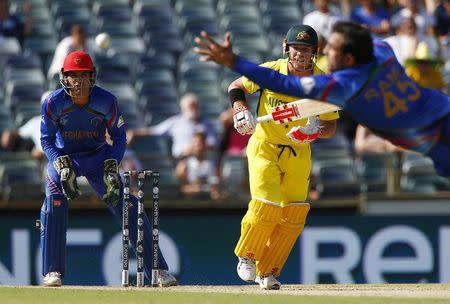 Afghanistan's bowler Shinwari dives for the ball off Australia's batsman Warner, as wicketkeeper Zazai watches on, during their Cricket World Cup match in Perth