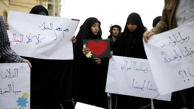 "Iranian students hold posters with Arabic that read, center left, ""yes yes to dialogue, no no to controversy,"" and center, ""Egypt,"" during a rally in support of solidarity with Egypt, in Tehran, Iran, Tuesday, April 9, 2013. Last week, a group of angry ultraconservative Salafis protesters threw rocks and tried to storm the residence of Iran's top diplomat in Cairo, after Iranian tourists arrived in Egypt on the first commercial flights between the two countries in 30 years. (AP Photo/Ebrahim Noroozi)"