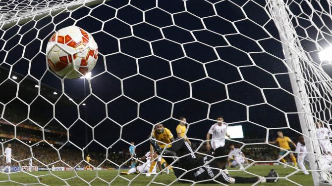 UAE's goalkeeper Majed Naser misses a save as Australia's Jason Davidson scores a goal against UAE during their Asian Cup semi-final soccer match at the Newcastle Stadium in Newcastle