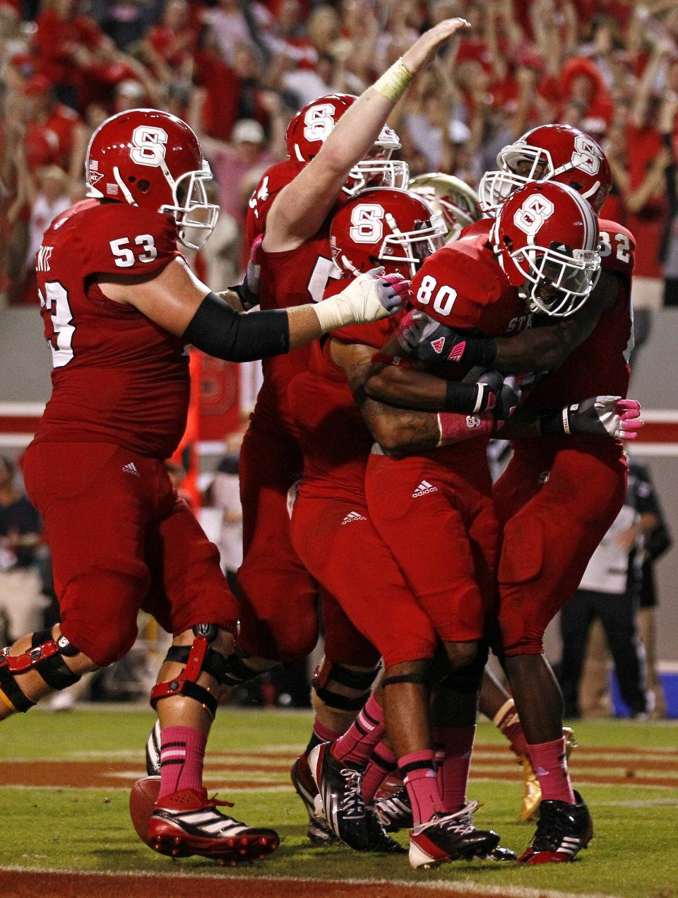 North Carolina State's Bryan Underwood (80) is congratulated by teammates after Underwood's touchdown to tie the game late in the second half of an NCAA college football game against Florida State in Raleigh, N.C., Saturday, Oct. 6, 2012. North Carolina State won 17-16. (AP Photo/Gerry Broome)