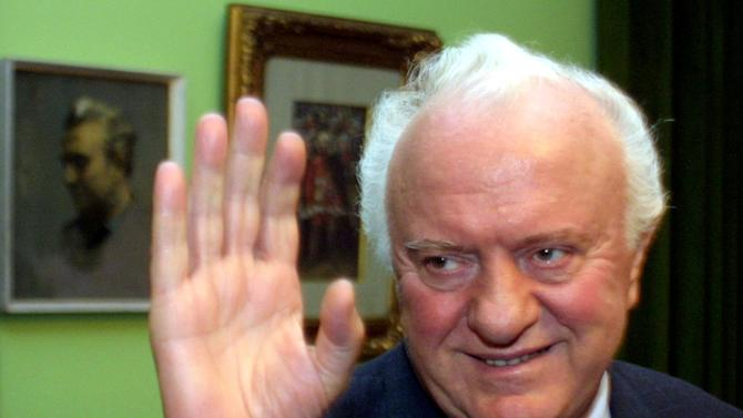 Former Georgian President Eduard Shevarnadze waves to journalists at his home outside Tbilisi, November 28, 2003