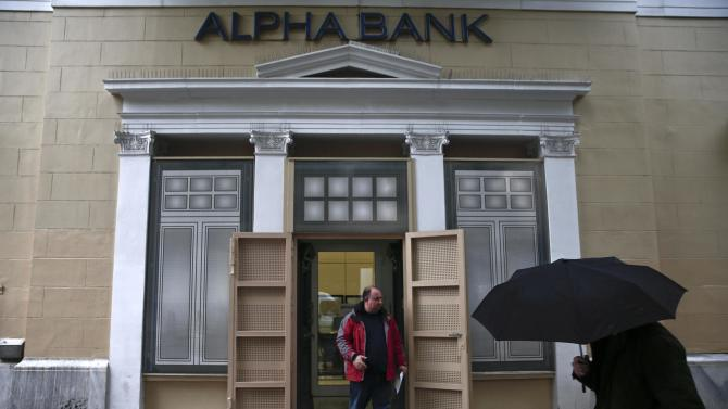 A man exits an Alpha Bank branch in Athens