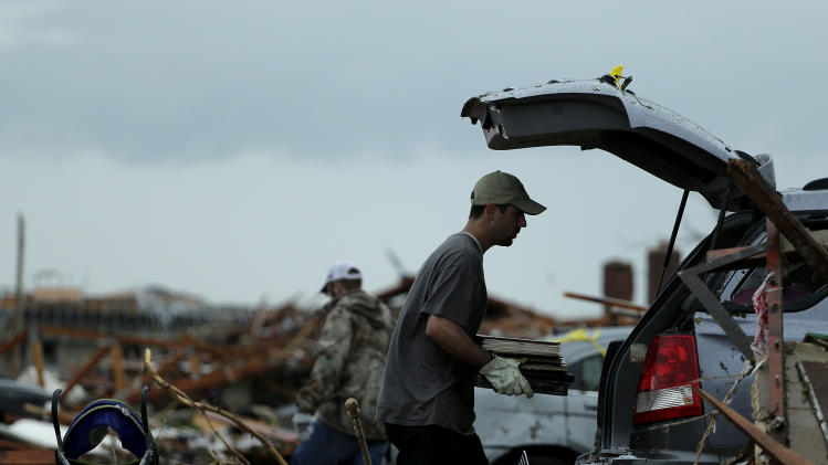 Justin Stehan salvages photographs from his tornado-ravaged home Tuesday, May 21, 2013, in Moore, Okla. A huge tornado roared through the Oklahoma City suburb Monday, flattening entire neighborhoods and destroying an elementary school with a direct blow as children and teachers huddled against winds. (AP Photo/Charlie Riedel)
