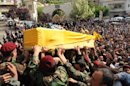 Hezbollah fighters in their military uniform, foreground, carry the coffin of Hezbollah fighter Hassan Faisal Shuker, 18, who was killed in a battle against Syrian rebels in the Syrian town of Qusair, during his funeral procession in his hometown of Nabi Sheet in the eastern Bekaa valley, Lebanon, Monday May 20, 2013. Fierce street fighting in Qusair, Syria, near the Lebanese border has killed at least 28 elite members of Lebanon's militant Hezbollah group, activists said Monday, as Syrian government forces pushed deeper into the strategic, opposition-held town. The barefaced Hezbollah involvement -- several funerals for group members were held in Lebanon Monday -- edges the war further into a regional sectarian conflict pitting the Middle East�s Iranian-backed Shiite axis against Sunnis. (AP Photo)