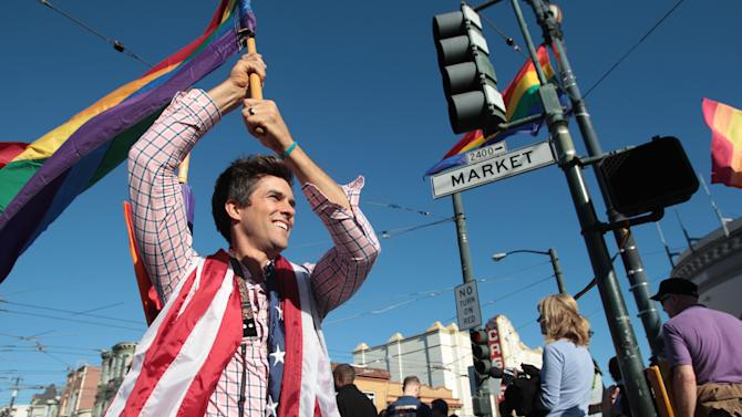 Nathan Frietas waves a rainbow flag at a celebration for the U. S. Supreme Court's ruling on Prop. 8 in the Castro District in San Francisco, on Wednesday, June 26, 2013. In a major victory for gay rights, the Supreme Court on Wednesday struck down a provision of a federal law denying federal benefits to married gay couples and cleared the way for the resumption of same-sex marriage in California. (AP Photo/Mathew Sumner)