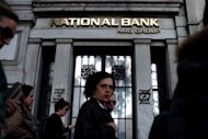 People walk outside a National Bank of Greece, in Athens. US stocks gave up early gains on positive US economic data to sink lower Wednesday as worries over Greece&#39;s future in the eurozone hit investor sentiment