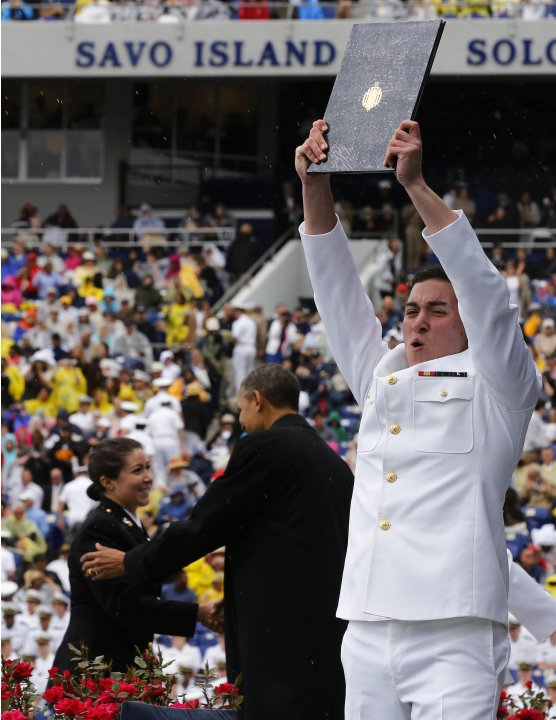 A graduate celebrates as U.S. President Barack Obama shakes hands at the U.S. Naval Academy commencement ceremony in Annapolis