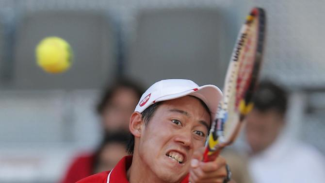 Kei Nishikori from Japan returns the ball during the match against Roger Federer from Switzerland at the Madrid Open tennis tournament, in Madrid, Thursday, May 9, 2013. (AP Photo/Andres Kudacki)
