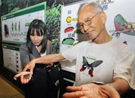 Taiwanese entomologist Chen Wei-shou (R) places a butterfly the hand of a visitor during a briefing held at the insect museum of Taipei&#39;s Cheng Kung High School. In some parts of Taiwan, Chen said, butterfly populations are now one hundredth of the level before industralisation
