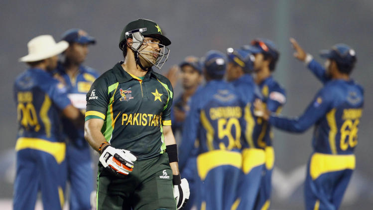 Pakistan's Umar Akmal, foreground, walks back to the pavilion after his dismissal by Sri Lanka's Suranga Lakmal during the opening match of the Asia Cup one-day international cricket tournament between them in Fatullah, near Dhaka, Bangladesh, Tuesday, Feb. 25, 2014. (AP Photo/A.M. Ahad)