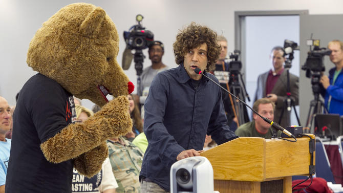 "Environmentalist Jim Brown, right, uses a bear's inability to speak to exemplify ""animals rights,"" as he addresses the California Coastal Commission meeting in Santa Monica, Calif. Wednesday, Nov. 14, 2012. The California Coastal Commission is weighing whether to grant a permit to the Pacific Gas & Electric Co. to conduct seismic imaging off the coast of the Diablo Canyon nuclear plant. (AP Photo/Damian Dovarganes)"