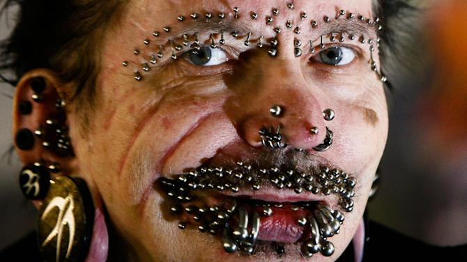 FILE- In this Saturday, Dec. 4, 2010 file photo, German Rolf Buchholz shows his face with 168 piercings as he visits the 20th Tattoo Convention in Berlin. A Dubai nightclub that hoped to feature Buchholz, who holds the world record for having the most piercings, said in an emailed statement Sunday, Aug. 17, 2014, that he was refused entry to the Gulf city because of security concerns. The German man now has 453 piercings, including many in his face and genitals, according to Guinness World Records. (AP Photo/Markus Schreiber, File)