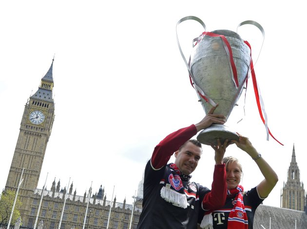 Bayern Munich supporters hold a model of the Champions League trophy as they walk near the Houses of Parliament in central London